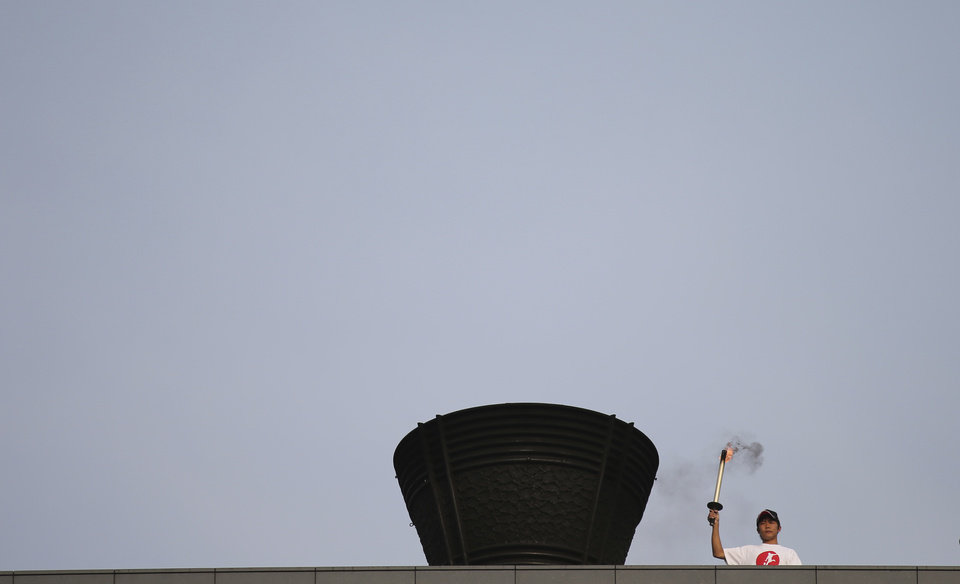 Photo - A toach-bearer and high school rugby player Tatsuki Kawagoe prepares to light flame on the Olympic cauldron  at the National Stadium in Tokyo, Sunday, May 25, 2014. Tokyo's National Stadium, the centerpiece of the 1964 Summer Olympics, hosted its final sporting event on Sunday before it is demolished to make way for a new 80,000-seat structure that will be the main venue of the 2020 Olympics. (AP Photo/Eugene Hoshiko)