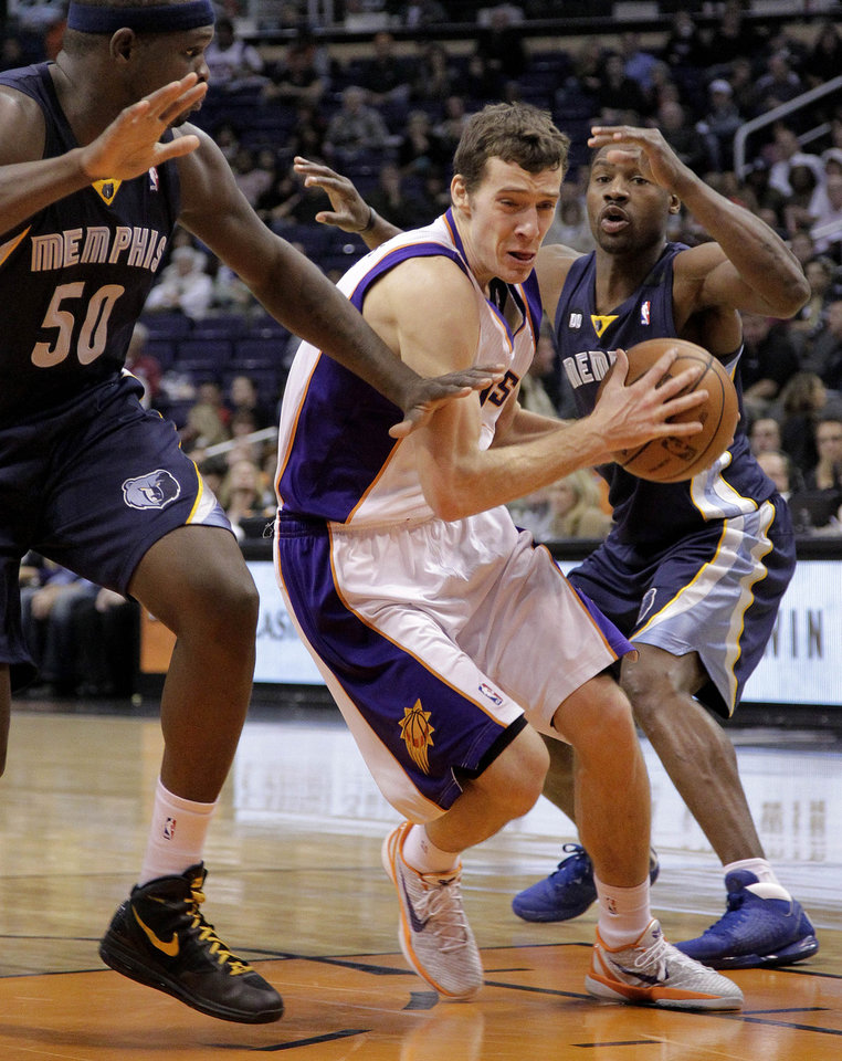 Phoenix Suns' Goran Dragic, of Slovenia, drives past Memphis Grizzlies' Zach Randolph (50) and Rudy Gay, right, during the second half of an NBA basketball game on Wednesday, Dec. 12, 2012, in Phoenix. (AP Photo/Matt York)