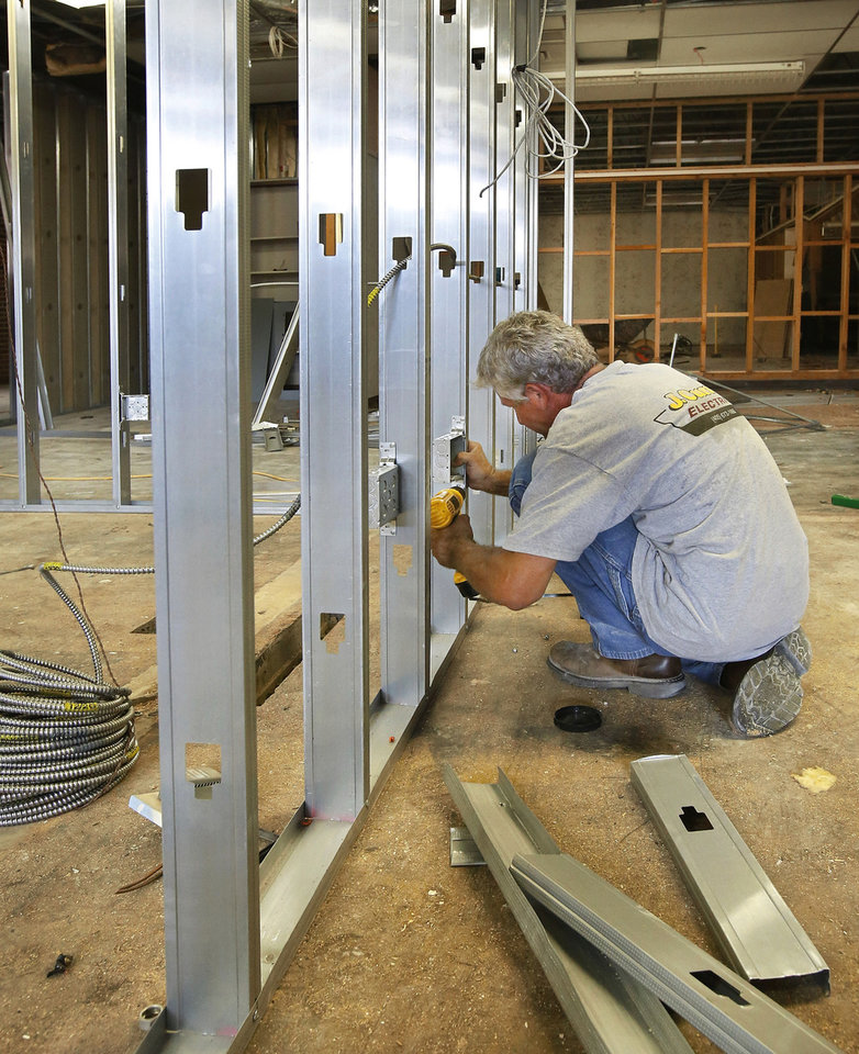 An electrician attaches an electrical box to metal studs. Workers are converting rooms at Moore's Central Junior High School into classrooms to accommodate elementary students displaced by the May 20 tornado.    Photo  by Jim Beckel, The Oklahoman. <strong>Jim Beckel - THE OKLAHOMAN</strong>
