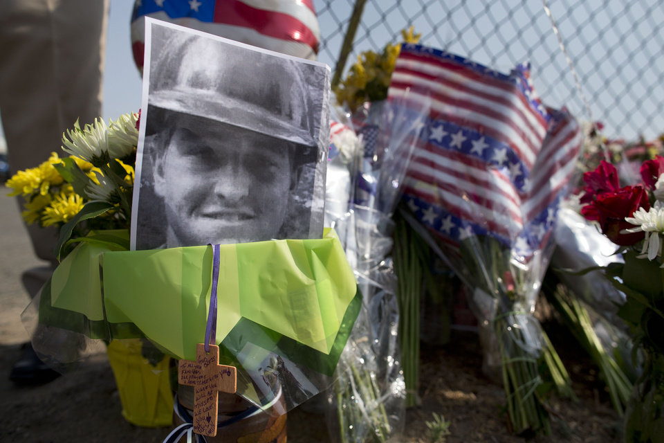 Photo - A photo of one of the 19 Granite Mountain Hot Shot crew members who was killed fighting a wild land fire near Yarnell, Ariz. on Sunday, sits at a makeshift memorial outside the crew's fire station, Monday, July 1, 2013 in Prescott, Ariz. An out-of-control blaze overtook the elite group of firefighters trained to battle the fiercest wildfires, killing 19 members as they tried to protect themselves from the flames under fire-resistant shields. The disaster Sunday afternoon all but wiped out the 20-member Hotshot fire crew leaving the city's fire department reeling. (AP Photo/Julie Jacobson)