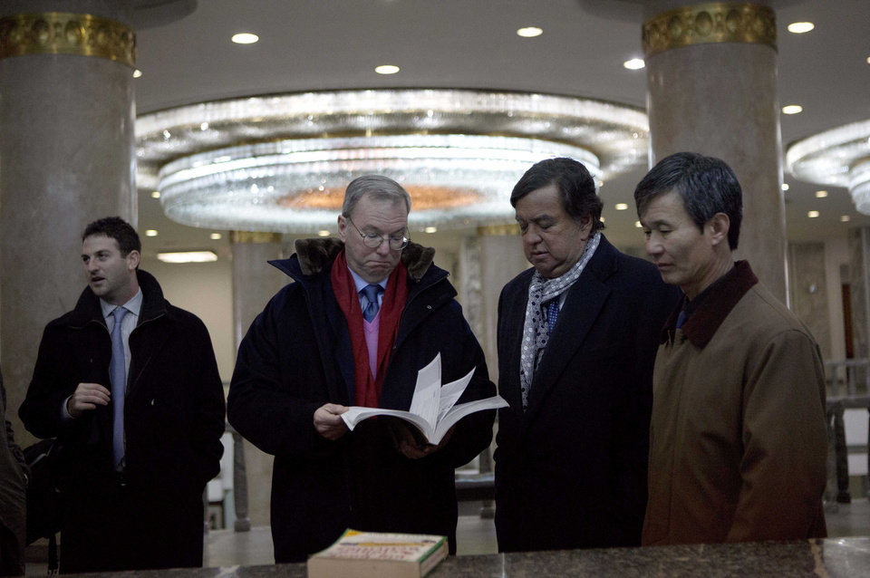 Photo - Executive Chairman of Google, Eric Schmidt, second from left, and former Governor of New Mexico Bill Richardson, second from right,  look through an information technology text book at the Grand People's Study House in Pyongyang, North Korea on Wednesday, Jan. 9, 2013. At left is director of Google Ideas think tank, Jared Cohen. The textbook is titled