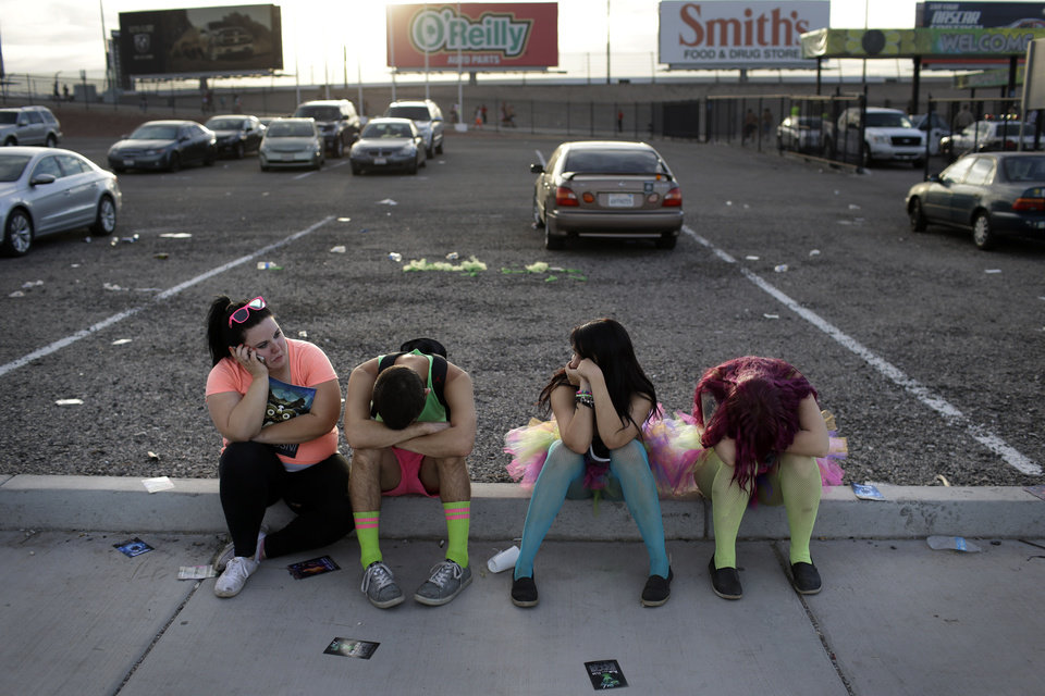 Photo - After a long night of partying at the Electric Daisy Carnival, festival goers rest on a curb outside of the Las Vegas Motor Speedway, early Saturday, June 21, 2014, in Las Vegas. Many of the attendees will return to their home or lodging to rest during the day before returning for another night. (AP Photo/John Locher)