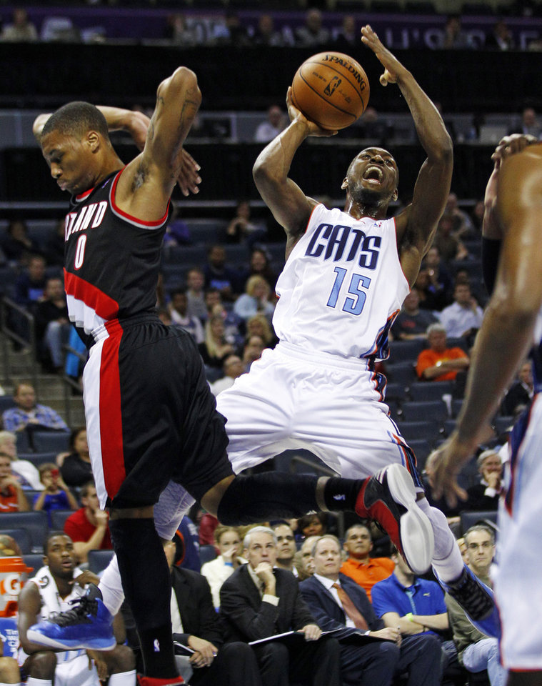 Photo - Charlotte Bobcats' Kemba Walker (15) shoots over Portland Trail Blazers' Damian Lillard (0) during the first half of an NBA basketball game in Charlotte, N.C., Monday, Dec. 3, 2012. (AP Photo/Chuck Burton)
