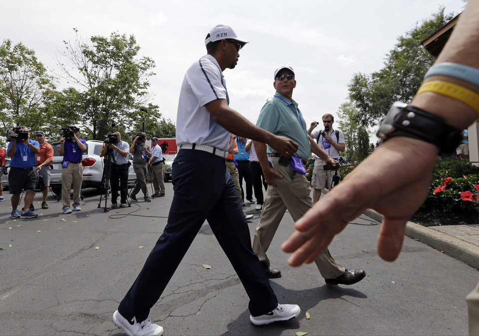 Photo - Tiger Woods arrives for a practice round for the PGA Championship golf tournament at Valhalla Golf Club on Wednesday, Aug. 6, 2014, in Louisville, Ky. The tournament is set to begin on Thursday. (AP Photo/David J. Phillip)