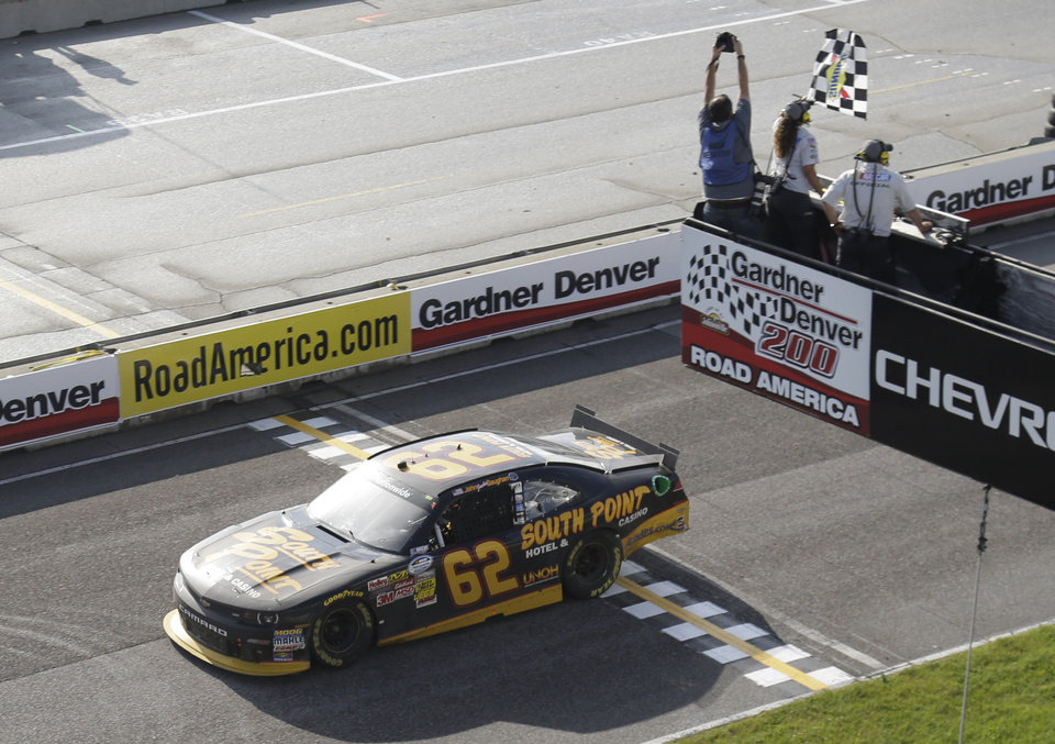 Photo - Brendan Gaughan takes the checkered flag to win the NASCAR Nationwide series auto race at Road America in Elkhart Lake, Wis., Saturday, June, 21, 2014. (AP Photo/Jeffrey Phelps)