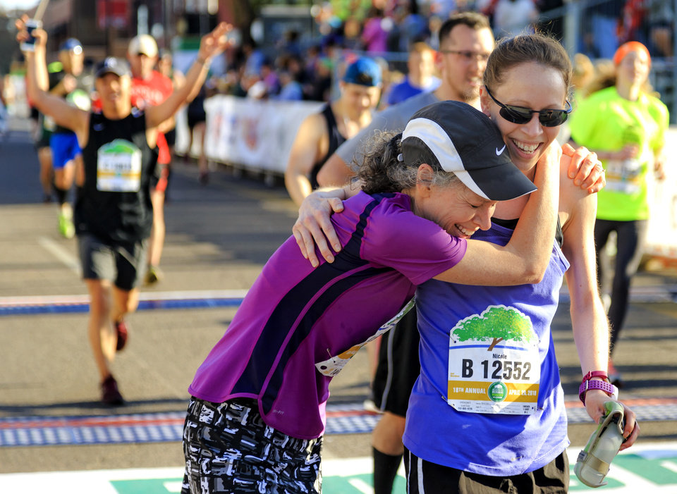 Photo - Karen Leroux, left, and Nicole Esler celebrate as they cross the finish line for the half marathon during the Oklahoma City Marathon in Oklahoma City, Okla. on Sunday, April 29, 2018.  . Photo by Chris Landsberger, The Oklahoman