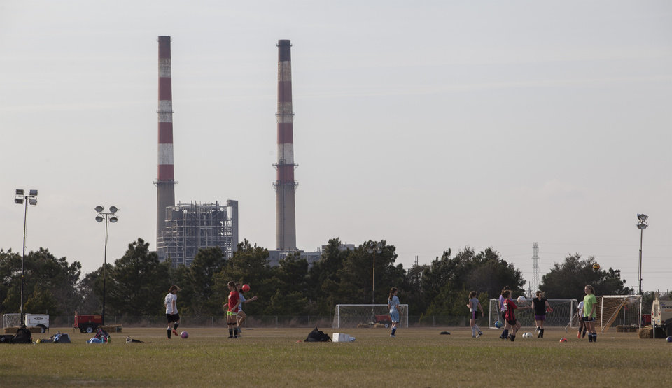 Photo - Girls play on a soccer fields near the L.V. Sutton Complex operated by Duke Energy in Wilmington, N.C., on Wednesday, Feb. 19, 2014. Members of the Flemington Road community near the plant, feel the facility could be polluting well water with spill off and seepage from large coal ash ponds.   (AP Photo/Randall Hill)