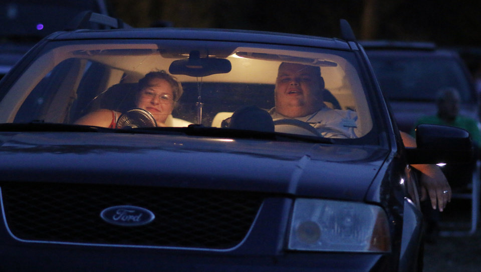 Photo - Lydia and Jonathan Philpott watch the start of the movie at the Airline Drive-in movie theater in Ponca City Thursday, August 14, 2014. Photo by Doug Hoke, The Oklahoman