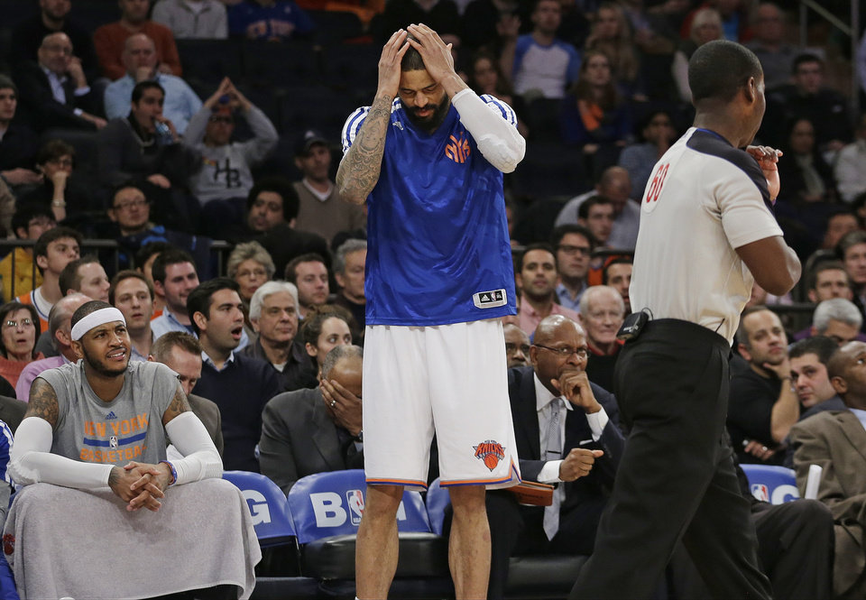 New York Knicks' Carmelo Anthony, left, and Tyson Chandler, center, react to a call by referee James Williams (60) during the second half of an NBA basketball game, Wednesday, Feb. 5, 2014, in New York. The Trail Blazers on the game 94-90.(AP Photo/Frank Franklin II)