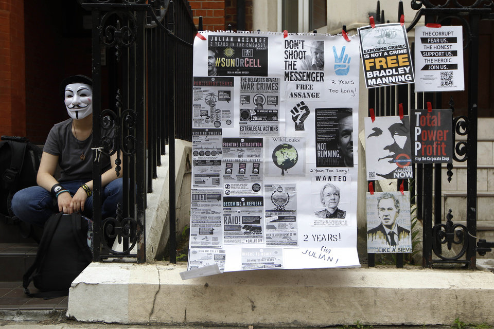 Photo - A supporter of WikiLeaks founder Julian Assange holds a vigil outside the Ecuadorian Embassy in London to mark his two years of refuge at the embassy, Thursday, June 19, 2014. Julian Assange entered the embassy in June 2012 to gain political asylum to prevent him from being extradited to Sweden, where he faces allegations of sex crimes, which he denies. (AP Photo/Sang Tan)