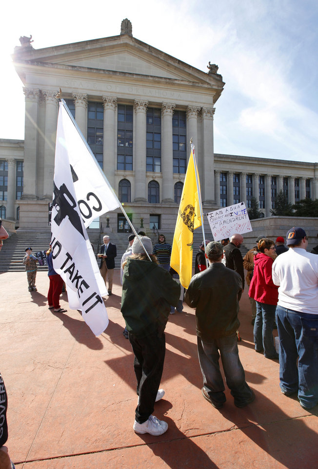 Protesters carry flags and signs as members of the Oklahoma Defense Force hold a rally on the north side of the state Capitol in Oklahoma City. Photo by Paul B. Southerland, The Oklahoman PAUL B. SOUTHERLAND - PAUL B. SOUTHERLAND