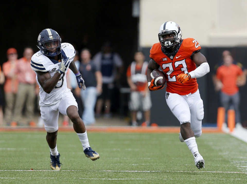 Photo - Oklahoma State's Rennie Childs (23) rushes for a touchdown as Pittsburgh's Jordan Whitehead (9) chases him down during a college football game between the Oklahoma State Cowboys (OSU) and the Pitt Panthers at Boone Pickens Stadium in Stillwater, Okla., Saturday, Sept. 17, 2016. Photo by Sarah Phipps, The Oklahoman