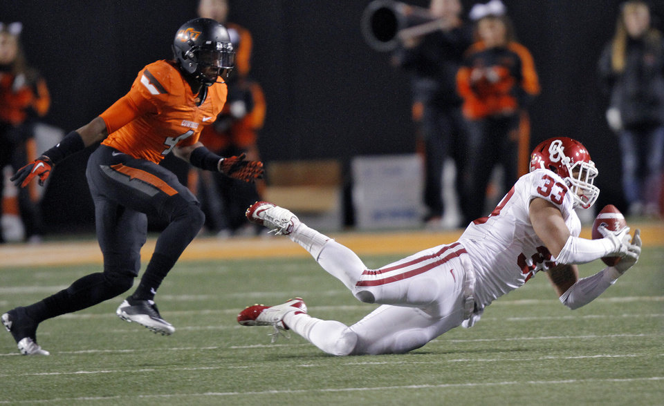 Oklahoma\'s Trey Millard (33) makes a reception in front of Oklahoma State\'s Justin Gilbert (4) during the Bedlam college football game between the Oklahoma State University Cowboys (OSU) and the University of Oklahoma Sooners (OU) at Boone Pickens Stadium in Stillwater, Okla., Saturday, Dec. 3, 2011. Photo by Chris Landsberger, The Oklahoman