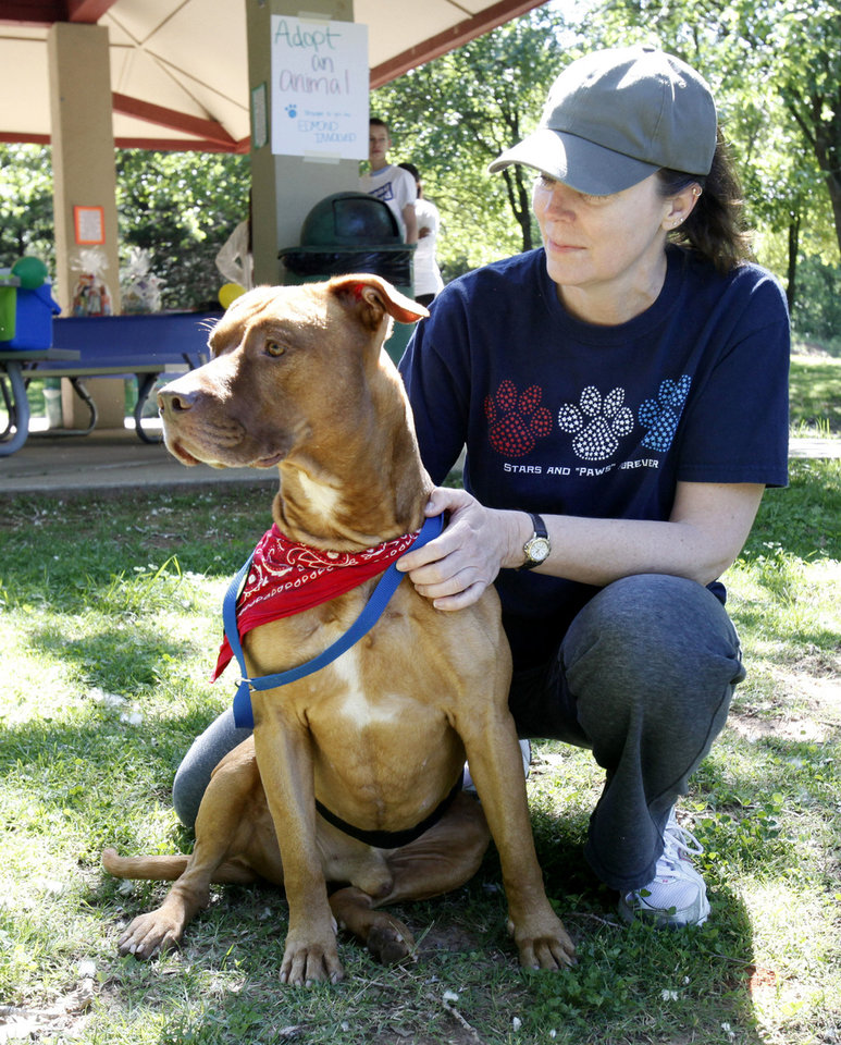Lauri McDougall, with Paws for Life, shows off Cooper during an animal adoption carnival Saturday to benefit the Edmond animal welfare shelter. PHOTO BY PAUL HELLSTERN, THE OKLAHOMAN