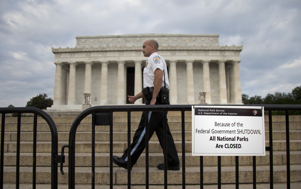 Photo - A US Park Police officer walks behind a barricade with sign reading