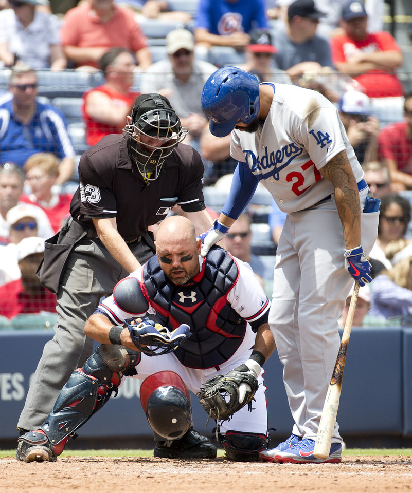 Photo - Los Angeles Dodgers' Matt Kemp (27) checks on Atlanta Braves catcher Gerald Laird (11) after he was hit with a foul ball in the third inning of a baseball game Thursday, Aug. 14, 2014, in Atlanta. Laird was not injured. (AP Photo/John Bazemore)
