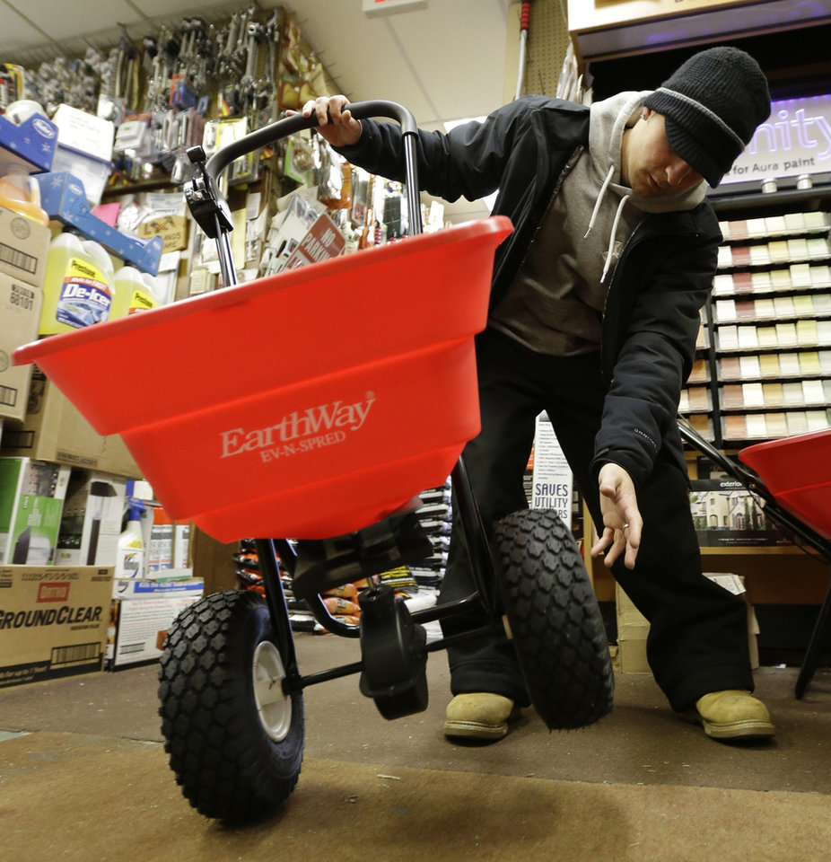 Photo - Marco Iuele inspects a salt spreader while shopping at Meadowlands Hardware, Thursday, Jan. 2, 2014, in East Rutherford, N.J. Snow and bone-chilling temperatures are expected for Thursday night with substantial accumulation predicted. (AP Photo/Julio Cortez)
