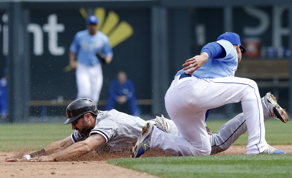 Photo - Chicago White Sox' Adam Eaton, left, is tagged out by Kansas City Royals second baseman Omar Infante, right, during the third inning of a baseball game at Kauffman Stadium in Kansas City, Mo., Sunday, April 6, 2014. Eaton was caught stealing on the play. (AP Photo/Orlin Wagner)