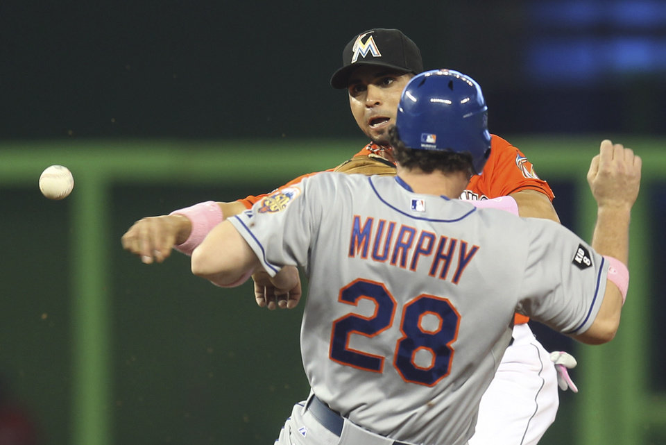 Photo -   After New York Mets runner Daniel Murphy (28) is forced out at second as Miami Marlins second baseman Omar Infante throws to first to get Ronny Cedeno out in a second-inning double play in a baseball game in Miami, Sunday, May 13, 2012. (AP Photo/J Pat Carter)