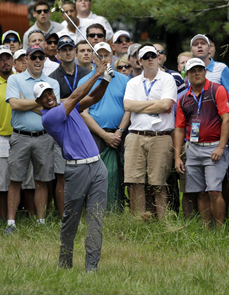 Photo - Tiger Woods hits from rough on the first2 hole during the first round of the PGA Championship golf tournament at Valhalla Golf Club on Thursday, Aug. 7, 2014, in Louisville, Ky. (AP Photo/John Locher)