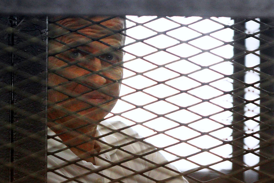 Photo - Al-Jazeera journalist Peter Greste looks out from the defendant's cage during a sentencing hearing in a courtroom in Cairo, Egypt, Monday, June 23, 2014. An Egyptian court on Monday convicted three journalists from Al-Jazeera English and sentenced them to seven years in prison each on terrorism-related charges, bringing widespread criticism that the verdict was a blow to freedom of expression. The three, Australian Peter Greste, Canadian-Egyptian Mohamed Fahmy and Egyptian Baher Mohammed, have been detained since a December raid on their Cairo hotel room, which they were using as an office as they covered protests by supporters of the ousted Islamist president. The raid was part of a broad crackdown against Islamists and the Muslim Brotherhood.(AP Photo/Ahmed Abd El Latif, El Shorouk Newspaper) EGYPT OUT