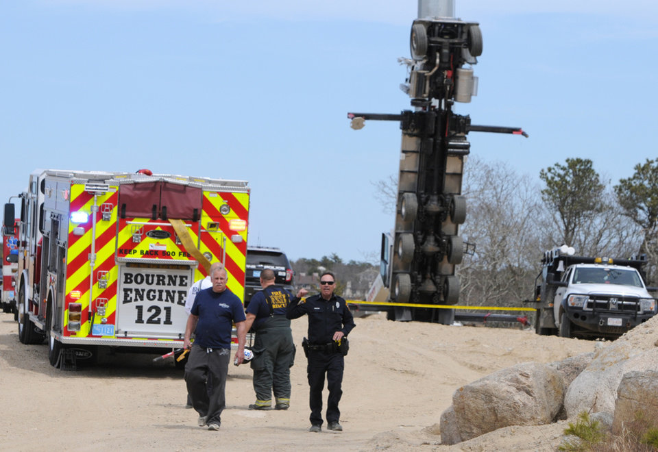 Photo - Authorities work on the scene of a fatal accident where two workers died in Bourne, Mass., Saturday, April 12, 2014. Their bucket truck apparently tipped over while they were in the basket more than 100 feet in the air at a Cape Cod site. (AP Photo/Cape Cod Times, Steve Heaslip)
