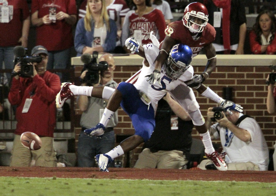 Photo - Justin Brown (19) and Greg Brown (5) colide on a pass attempt during the college football game between the University of Oklahoma Sooners (OU) and the University of Kansas Jayhawks (KU) at Gaylord Family-Oklahoma Memorial Stadium in Norman, Okla., on Saturday, Oct. 20, 2012. Photo by Steve Sisney, The Oklahoman