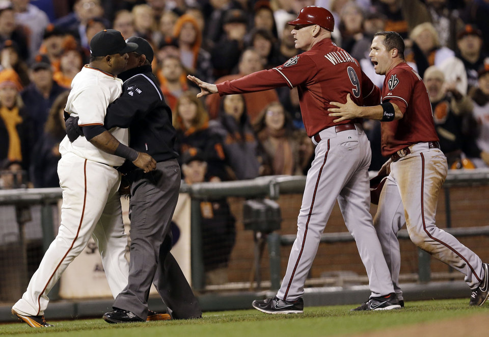 Photo -   San Francisco Giants third baseman Pablo Sandoval, left, is held back by third base umpire Greg Gibson as he argues with Arizona Diamondbacks' John McDonald, right, being held back by third base coach Matt Williams, second from left, after McDonald and Sandoval collided on a ground ball by Adam Eaton during the eighth inning of a baseball game on, Wednesday, Sept. 5, 2012 in San Francisco. (AP Photo/Marcio Jose Sanchez)