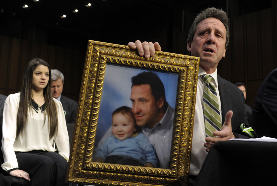 Neil Heslin, the father of a six-year-old boy who was slain in the Sandy Hook massacre in Newtown, Conn., on Dec. 14, holds a picture of himself with his son Jesse and wipes his eye while testifying on Capitol Hill in Washington, Wednesday, Feb. 27, 2013, before the Senate Judiciary Committee on the Assault Weapons Ban of 2013.  At left is Carlee Soto, sister of slain Sandy Hook Elementary teacher Victoria Soto. (AP Photo/Susan Walsh)