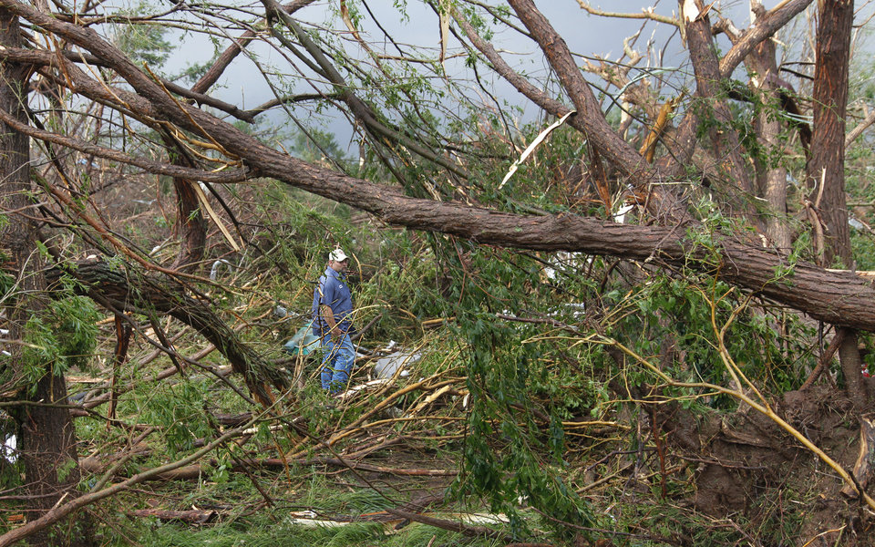 Photo - A passing motorist volunteers his time to the search efforts in a wooded area where two fatalities were confirmed after a tornado swept cars off of I-40 west of El Reno, Tuesday, May 24, 2011. Photo by Chris Landsberger, The Oklahoman ORG XMIT: KOD