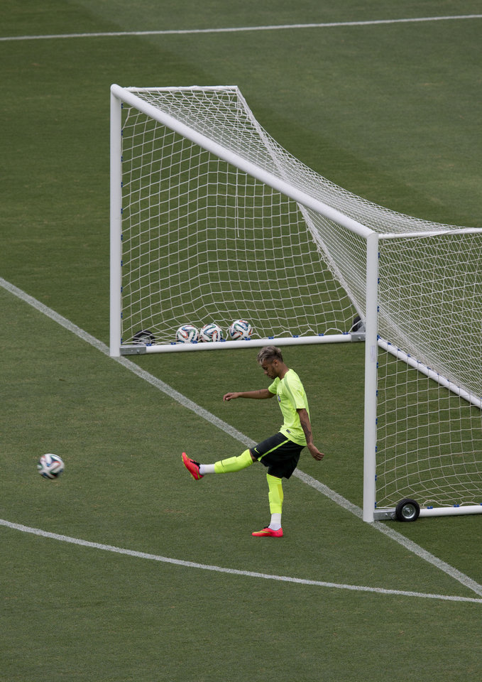 Photo - Brazil's Neymar kicks the ball during an official training session the day before the group A World Cup soccer match between Brazil and Mexico, at the Arena Castelao in Fortaleza, Brazil, Monday, June 16, 2014. (AP Photo/Eduardo Verdugo)
