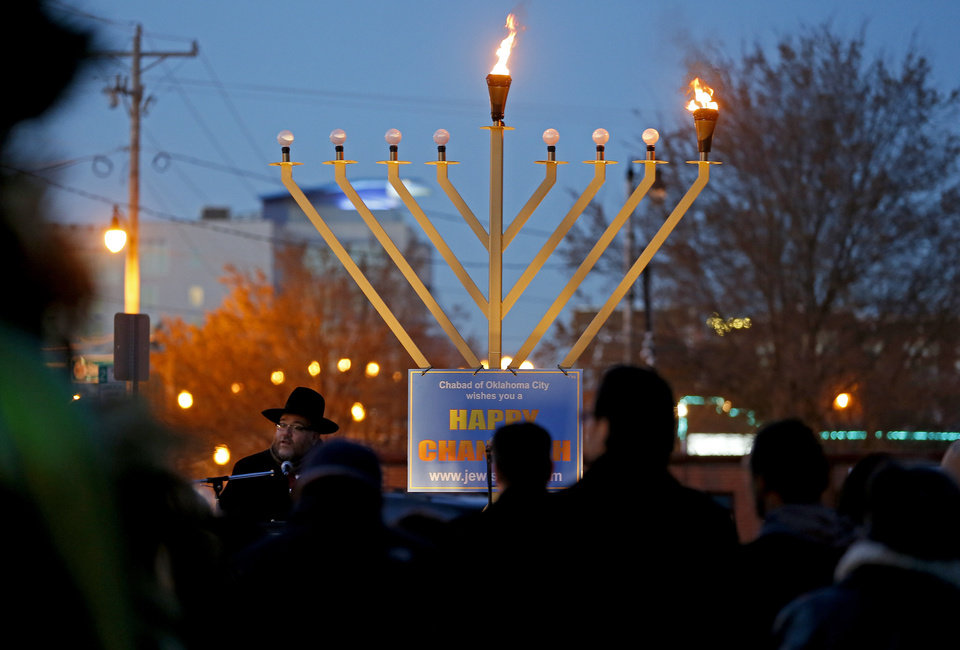 Photo - Rabbi Ovadia Goldman, spiritual leader of the Chabad Community Center for Jewish Life and Learning, addresses a crowd during a 2013 Bricktown Menorah Lighting event to celebrate the first night of  Hanukkah outside the Chickasaw Bricktown Ballpark in Oklahoma CIty. [Photo by Bryan Terry, The Oklahoman]