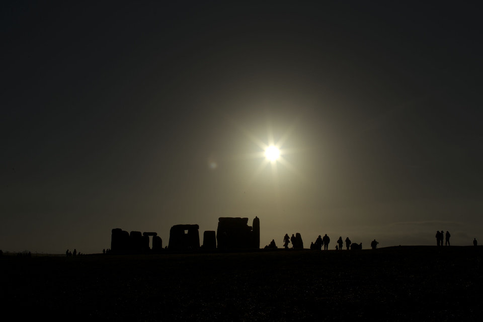 Photo - People are silhouetted as the sun rises above the ancient stone circle of Stonehenge, in southern England, as access to the site is given to druids, New Age followers and members of the public on the annual Winter Solstice, Friday, Dec. 21, 2012.  Doomsday hour is here and so still are we.  According to legend, the ancient Mayans' long-count calendar ends at midnight Thursday, ushering in the end of the world. Didn't happen.