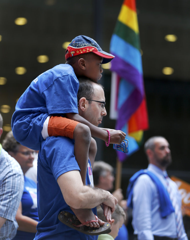 Photo - George Sloan, from Chicago, holds his son Sloan D'Souza on his shoulders as they attend a rally in support of gay marriage in Wisconsin and Indiana, at the federal plaza Monday, Aug. 25, 2014, in Chicago. The Chicago-based 7th U.S. Circuit Court of Appeals will hear arguments Tuesday on gay marriage fights from Indiana and Wisconsin, setting the stage for one ruling. Each case deals with whether statewide gay marriage bans violate the Constitution. (AP Photo/Charles Rex Arbogast)