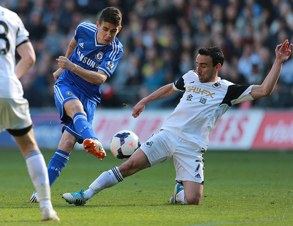 Photo - Chelsea's Oscar., left,  is tackled by Swansea City's Leon Britton during their English  Premier League match at the Liberty Stadium, Swansea Wales Sunday April 13, 2014. (AP Photo/David Davies/PA) UNITED KINGDOM OUT