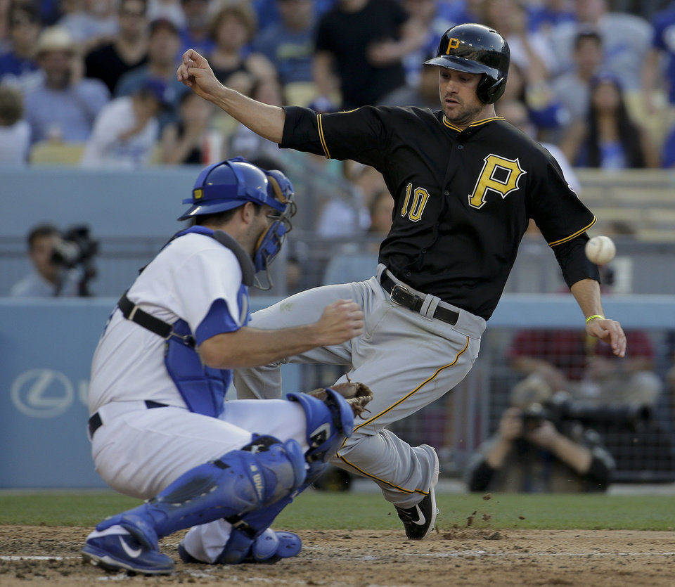 Photo - Pittsburgh Pirates' Jordy Mercer, right, scores past Los Angeles Dodgers catcher Drew Butera on a single by Travis Snider during sixth inning of a baseball in Los Angeles, Saturday, May 31, 2014. (AP Photo/Chris Carlson)