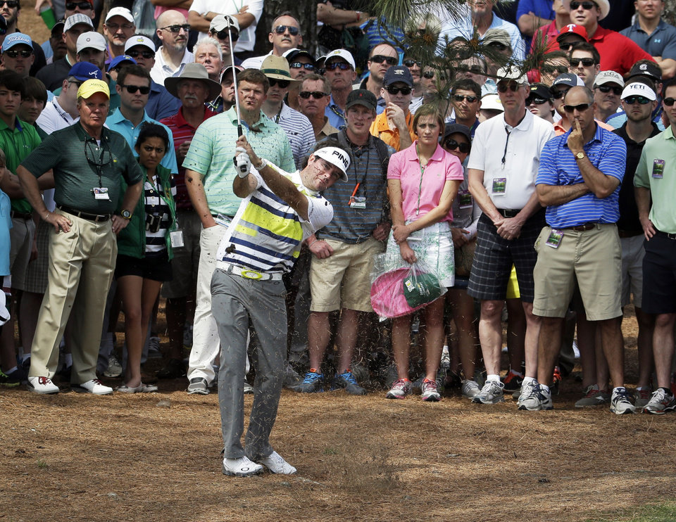 Photo - Bubba Watson hits out of the rough off the ninth fairway during the second round of the Masters golf tournament Friday, April 11, 2014, in Augusta, Ga. (AP Photo/Darron Cummings)