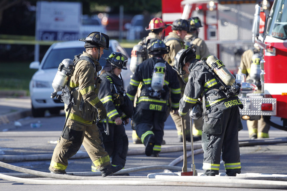 Photo - Firefighter work in front of  an apartment where the suspect in a theatre shooting lived in Aurora, Colo., on Friday, July 20, 2012. As many as 12 people were killed and 50 injured at a shooting at the Century 16 movie theatre on Friday.  The suspect is identified as 24-year-old James Holmes.  (AP Photo/Ed Andrieski) ORG XMIT: COEA117