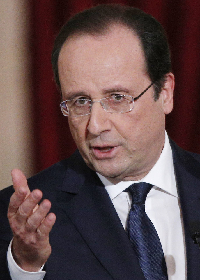 Photo - French President Francois Hollande addresses a reporter during his annual news conference, Tuesday, Jan.14, 2014 at the Elysee Palace in Paris. Hollande is promising to cut 50 billion euros in public spending over 2015-2017 to try to improve the indebted economy. Hollande, a Socialist, came to office in 2012 on pledges to avoid the painful austerity measures carried out by neighboring Spain and Italy. But France's economy has suffered two recessions in recent years and growth is forecast at an anemic 0.2 percent in 2013. (AP Photo/Christophe Ena)