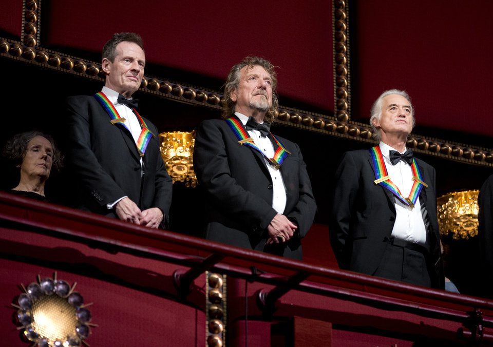 Photo - Rock band Led Zeppelin, from left, keyboardist/bassist John Paul Jones, singer Robert Plant, guitarist Jimmy Page, stand as the Star Spangled Banner is played during the Kennedy Center Honors Gala at the Kennedy Center in Washington, Sunday, Dec. 2, 2012. While Led Zeppelin is being honored as a band, surviving members Jones, Page, and Plant, each received the Kennedy Center Honors. (AP Photo/Manuel Balce Ceneta)