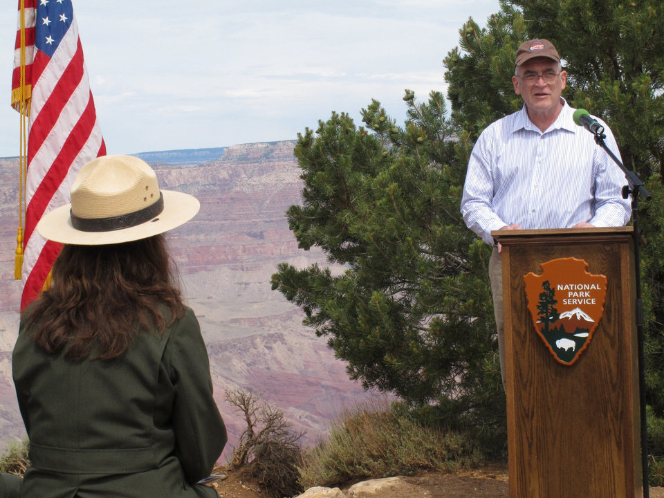 Photo - Mike Nelson, right, speaks about his uncle who was killed in a commercial airliner crash over Grand Canyon National Park in 1956, Tuesday, July 8, 2014. The ceremony at the Grand Canyon in northern Arizona marked the designation of the crash site as a National Historic Landmark. (AP Photo/Felicia Fonseca)