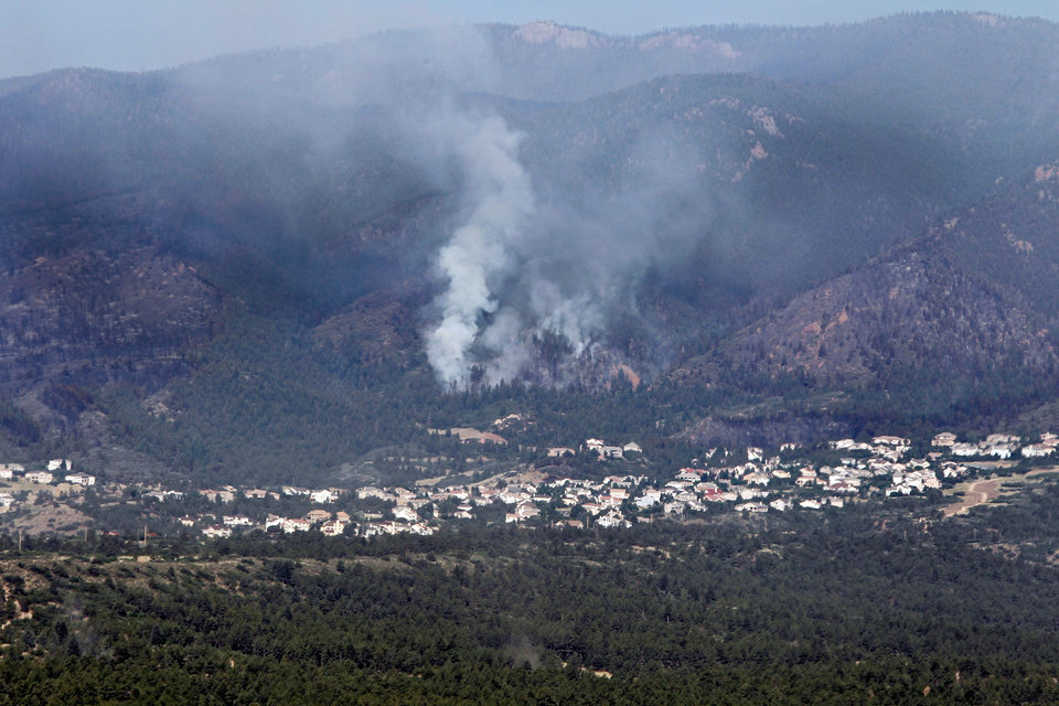 Photo -   The Waldo Canyon wildfire burns on the side of a mountain above a housing development at the U.S. Air Force Academy north of Colorado Springs, Colo., on Thursday, June 28, 2012. Hundreds of homes have been destroyed by an out-of-control Colorado wildfire that has forced more than 30,000 people to flee, officials said Thursday. (AP Photo/Ed Andrieski)