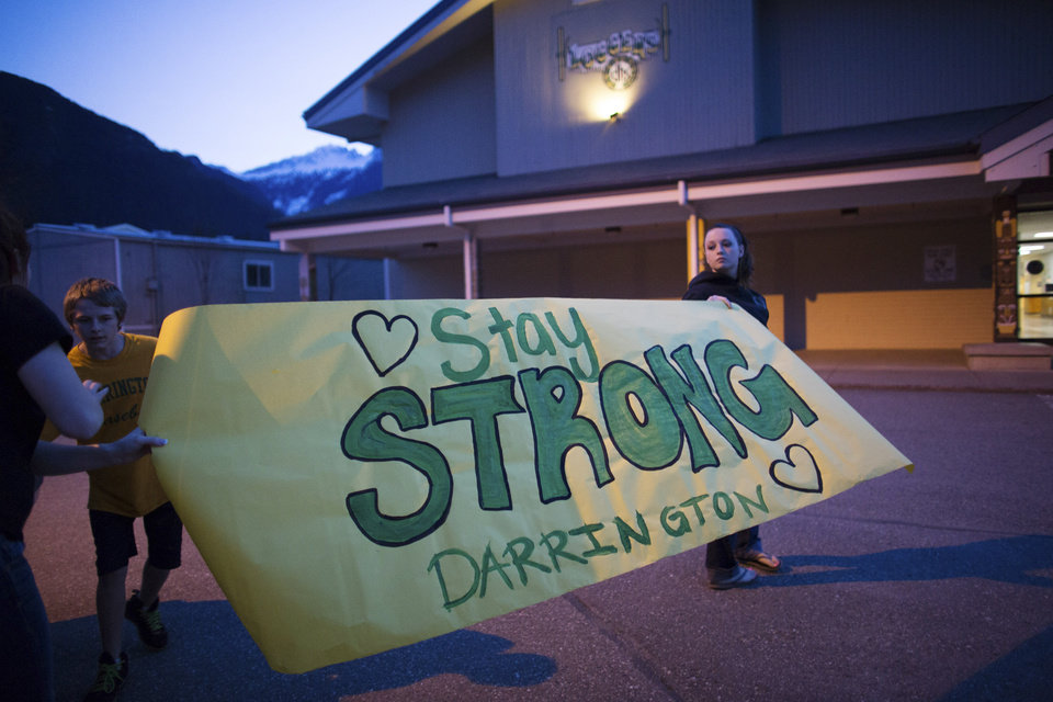 Photo - Shelby Stafford, 14, and Hailey Hudson, 17, hold a banner they made at Darrington High School in the wake of Saturday's mudslide in Snohomish County, near Oso, Wash on Monday, March 24, 2014. The search for survivors of Saturday's deadly mudslide grew Monday to include scores of people who were still unaccounted for as the death toll from the wall of trees, rocks and debris that swept through the rural community rose to at least 14.  (AP Photo/seattlepi.com, Joshua Trujillo)