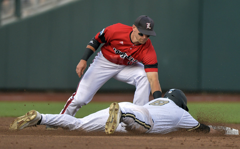 Photo - Vanderbilt's Rhett Wiseman (8) is caught stealing second base by Louisville second baseman Zach Lucas, top, in the second inning of an NCAA baseball College World Series game in Omaha, Neb., Saturday, June 14, 2014. (AP Photo/Ted Kirk)