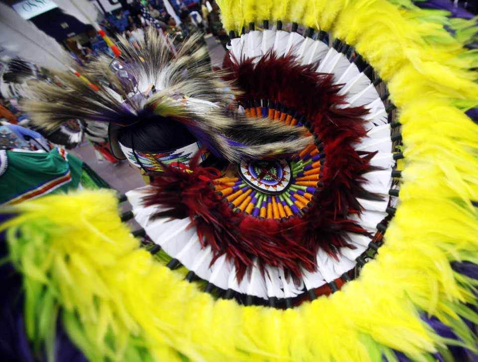 Photo -  The headdress of Michael Roberts, of Ada, is seen as he dances in the grand entrance at the University of Central Oklahoma's annual Spring Powwow. PHOTO BY K.T. KING, THE OKLAHOMAN   KT King -