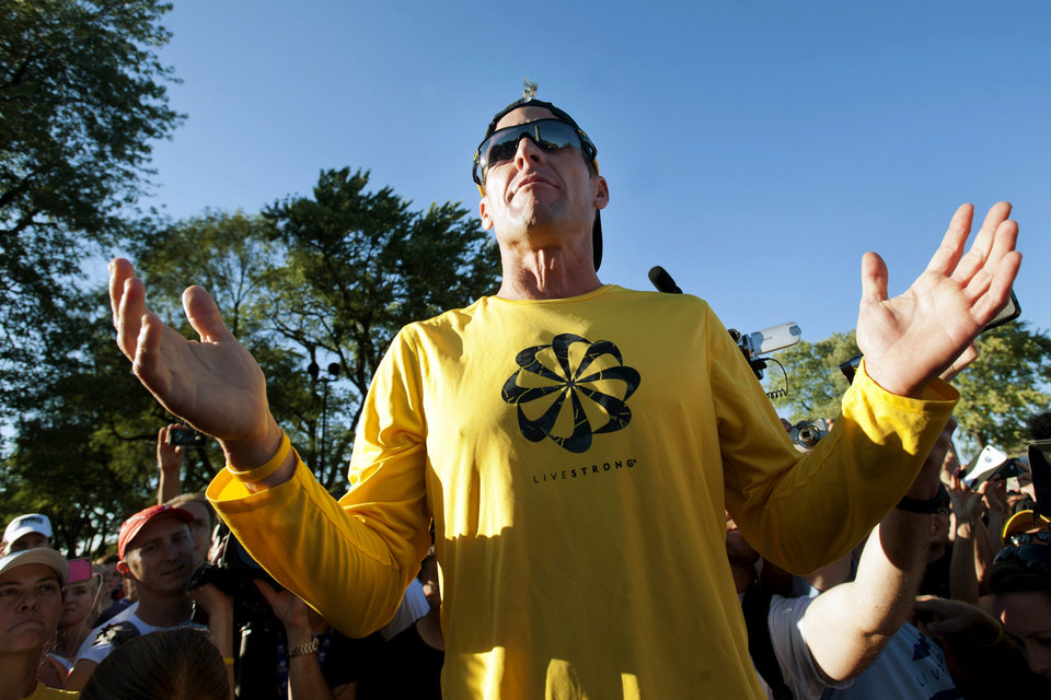 Photo - FILE - In this Aug. 29, 2012, file photo, Lance Armstrong talks to supporters prior to a run on Mont Royal Park in Montreal. Armstrong was diagnosed with cancer in 1996. Within minutes of Armstrong announcing he would step down as chairman of Livestrong, the foundation he created to support people with cancer, his longtime endorser Nike issued a statement saying it would be cutting sponsorship ties with the cyclist amid allegations of doping. Armstrong is said to be worth around $100 million, but most sponsors dropped him after USADA's scathing report _ at the cost of tens of millions of dollars. (AP Photo/The Canadian Press, Graham Hughes, File)