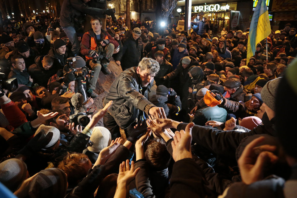 Photo - A Ukrainian protester gives pieces of the statue of Vladimir Lenin to people gathering around after toppling it, in Kiev, Ukraine, on Sunday, Dec. 8, 2013. The third week of protests continue Sunday with an estimated 200,000 Ukrainians occupying central Kiev to denounce President Viktor Yanukovych's decision to turn away from Europe and align this ex-Soviet republic with Russia. (AP Photo/Ivan Sekretarev)