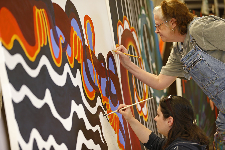 Oklahoma State University senior Casey Pankey, bottom, and senior Kris Swank work on a mural panel at Oklahoma State University on March 29. Artist Yatika Fields, a Stillwater native, is teaming up with OSU students to create a series of murals for a live painting event on Friday. Photo by Bryan Terry, The Oklahoman <strong>Bryan Terry</strong>