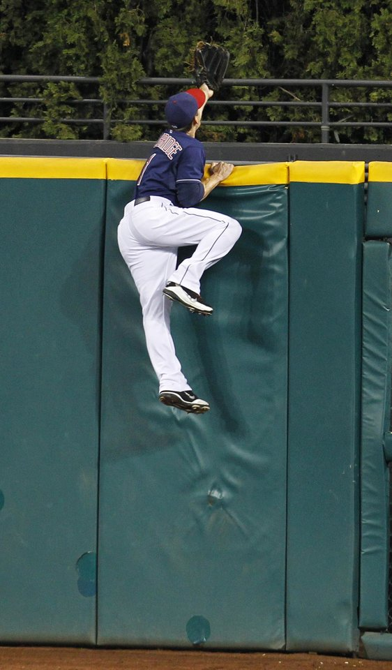Cleveland Indians' Brent Lillibridge hangs on to the wall as he watches the two-run home run by Chicago White Sox's Dayan Viciedo in the ninth of a baseball game, Tuesday, Oct. 2, 2012, in Cleveland. (AP Photo/Tony Dejak)