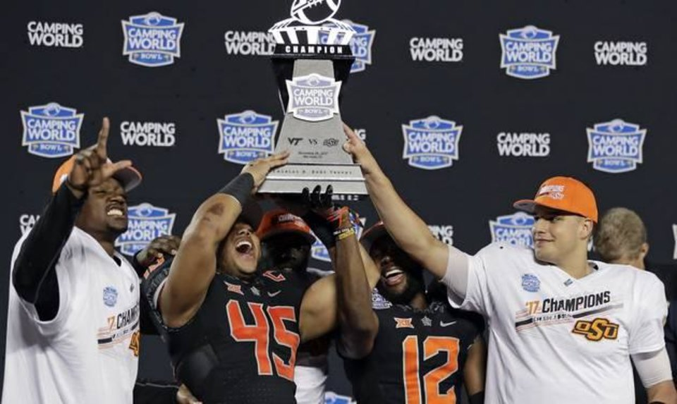 Photo - Oklahoma State players, from left, Tre Flowers, Chad Whitener (45), Kirk Tucker (12) and quarterback Mason Rudolph hold up the trophy after Oklahoma State defeated Virginia Tech 30-21 in the Camping World Bowl NCAA college football game Thursday, Dec. 28, 2017, in Orlando, Fla. (AP Photo/John Raoux)
